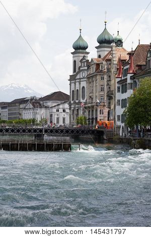 LUCERNE SWITZERLAND - MAY 04 2016: View towards the Jesuit Church located by the Reuss river in old town. It is widely believed to be the most beautiful Baroque church in Switzerland