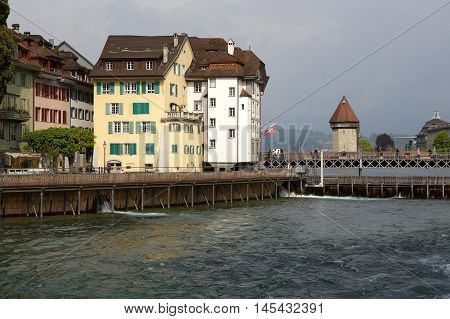 LUCERNE SWITZERLAND - MAY 02 2016: Needle Dam and in the background the buildings of the city. The Dam in the river Reuss was designed to maintain the level of water in Lake Lucerne