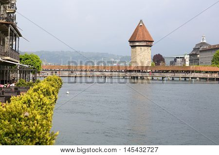 Lucerne Switzerland - May 02 2016: View towards the Chapel Bridge (Kapellbruecke) which joins two banks of the river Reuss together with the octagonal tall tower (Wasserturm) it is one of the Lucerne's most famous tourists attraction. A few people can be