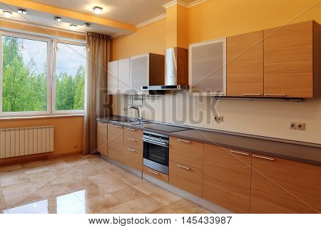 Luxury kitchen interior with orange walls stone floor and forest view