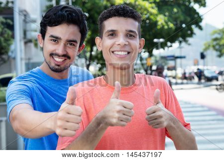 Latin man with mexican friend showing thumbs outdoor in the city in the summer