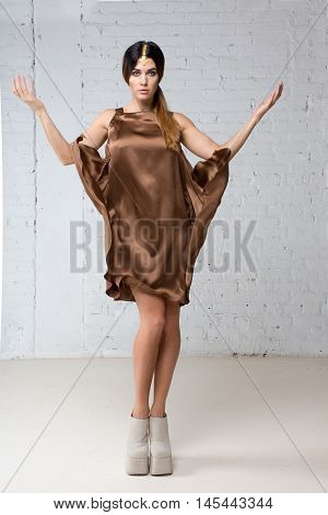 Woman model with Indian jewelery in brown silk dress and shoes posing, throws up the hem, creating waves in the studio full body