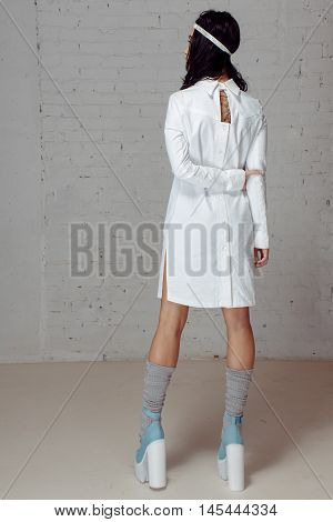 Woman in white dress- straitjacket turning away from photographer. She has beautiful white dress, grey knee socks and blue trankette