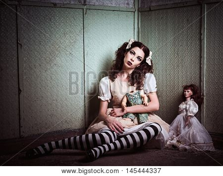 Strange sad girl with dolls sitting in the forsaken place
