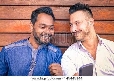 Multiracial young business men watching mobile phone screen and smiling - Indian man with caucasian friend having fun with smartphone - Concept of multicultural friendship