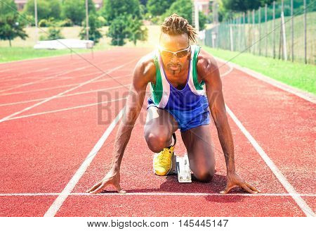 Afro american athlete ready to sprint at starting line - Runner kneeling on blocks of red athletics track - Concept of human concentration at sport competition - Soft vintage filter and sun reflection