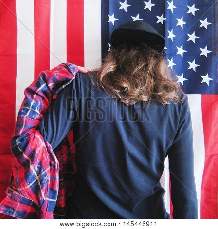 Lifestyle cropped portrait of young hipster girl dressing putting on plaid red shirt getting ready to go out. Casual clothes black pullover and black snapback cap with hair down on american flag background