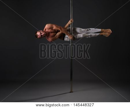 Studio photo of strong male dancer exercising on pole