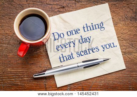 Do one thing every day that scares you - motivational handwriting on a napkin with a cup of coffee