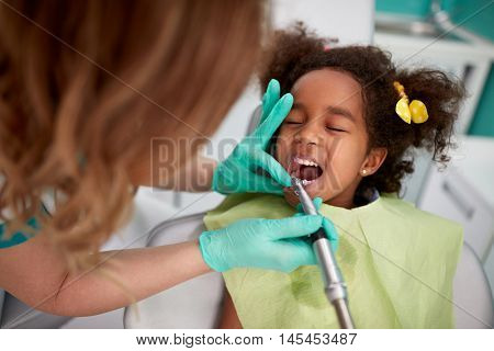 Nice female dentist patiently polish teeth to child in dental practice