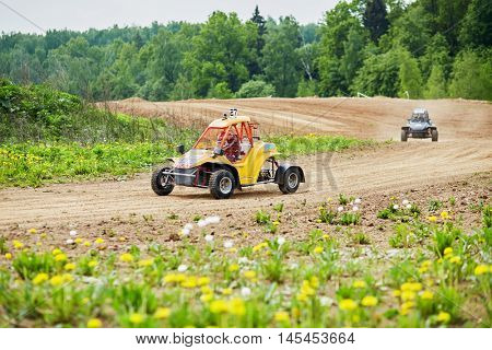 MYTISHCHI, RUSSIA - MAY 24, 2015: Two children on the racing cars compete on the track with a dirt road.