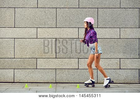 Beautiful young woman on roller skates and a pink helmet. Stylish girl in hipster retro roller skates skating in extreme urban park.