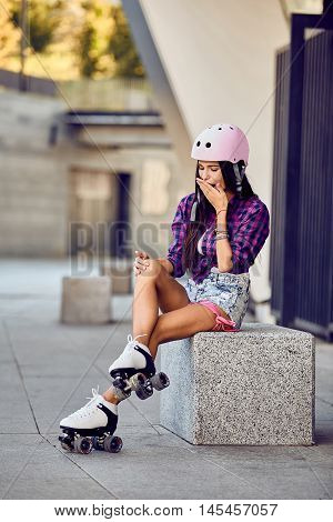 Girl hit a leg while roller skating in urban skate park. Young woman knee hurts. Stylish beautiful girl fit her knee during rollerblading. Young woman sitting on a stone bench.