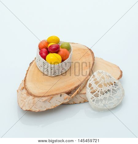 Candy in a casket in the form of heart on a white background on a cut tree
