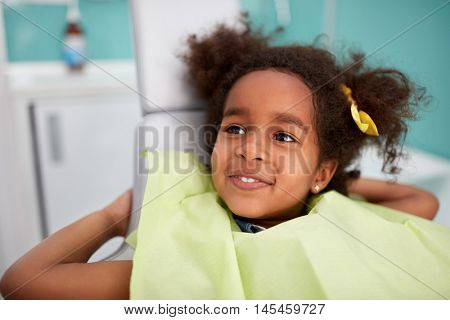 Portrait of satisfied child in dental chair after successful dental treatment