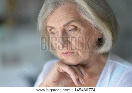 beautiful sad elderly woman in the room