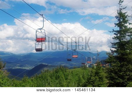 lifts line in the mountains on cloud background