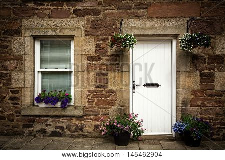 Door and window detail of a stone cottage facade, with hanging baskets and window boxes. Scotland, UK