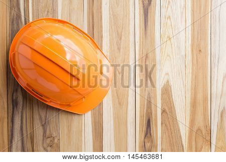 Orange safety engineer helmet gear on top of brown wooden table background. Empty copy space for inscription or objects