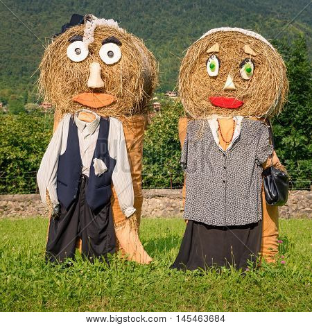 Lovely farmers Couple Puppets(straw dolls) made out of Hay Bale with typical peasant clothes in europe autumnsquare photo.