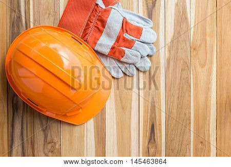 Orange safety engineer helmet gear and gloves on top of brown wooden table background. Empty copy space for inscription or objects