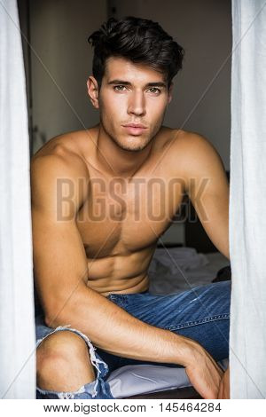Sexy handsome young man sitting shirtless in his bedroom next to window curtains