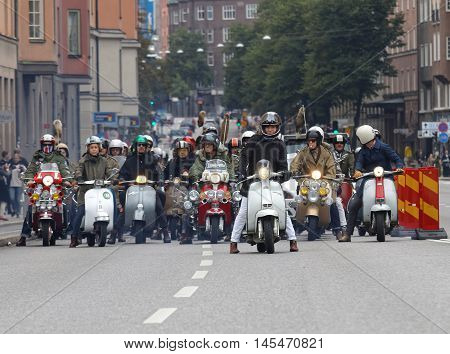 STOCKHOLM SWEDEN - SEPT 03 2016: Large group of mods on old fashioned vespas at the Mods vs Rockers event at the Saint Eriks bridge Stockholm Sweden September 03 2016