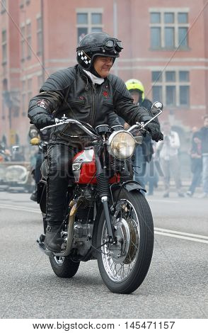 STOCKHOLM SWEDEN - SEPT 03 2016: GBiker wearing leather clothes on old fashioned motorcycle at the Mods vs Rockers event at the Saint Eriks bridge Stockholm Sweden September 02 2016