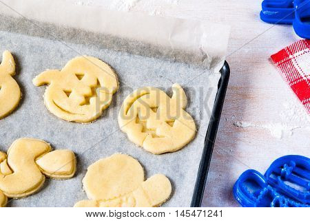 Making cookies for Halloween and Thanksgiving. Fun food for kids, a snack for a party. On a white wooden table pan with unbaked cookies