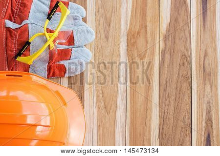 Safety helmetgloves and glasses and tool kit on wooden table background with copy space