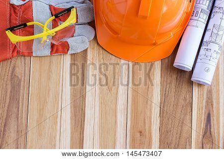 Protective gloves goggles and construction plan. Standard construction safety equipment on wooden table with copy space