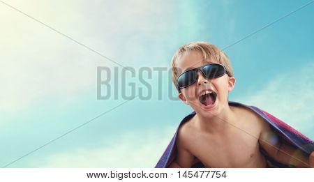 Boy wearing sunglasses wrapped in beach towel in summer sunshine