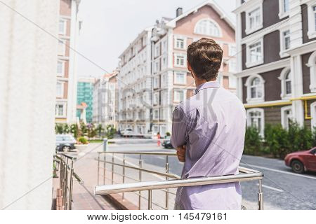 Young man is enjoying urban architecture outdoors. He is standing on balcony with relaxation. Focus on his back