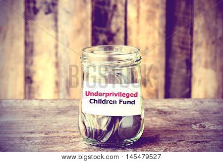 Coins in glass money jar with Underprivileged Children fund label financial concept. Vintage tone style