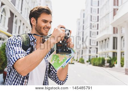 Happy young man is photographing architecture in town. He is standing and holding map. Traveler in smiling