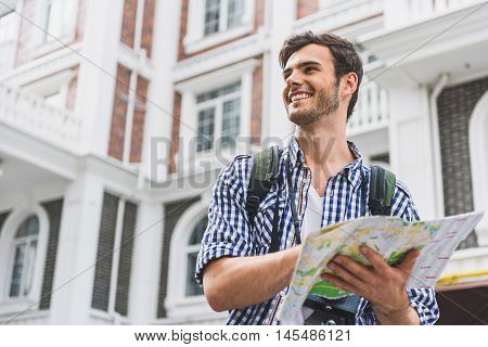 Joyful male tourist is looking for correct direction. He is using map and laughing