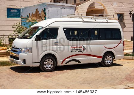 EGYPT, SHARM EL SHEIKH - JULY 20, 2015: Sharm el-Sheikh is holiday resort and significant centre for tourism in Egypt. White commercial passenger mini bus waiting for tourists