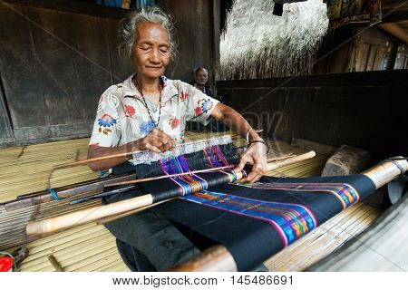 FLORES, INDONESIA - AUGUST 22, 2016: A woman weaves ikat to sell in Bena traditional village in Bajawa, Flores, Indonesia.