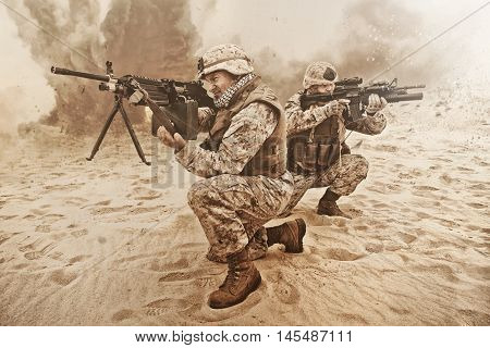 two US marines aim at different directions covering each other