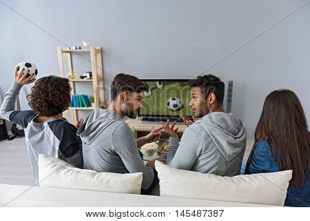 Cheerful two men are discussing football match with aspiration. Women are sitting on sofa and watching tv with concentration
