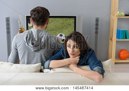 Young woman is bored while her husband is watching tv. She is sitting on sofa and looking forward with sadness. Man is drinking beer and looking at screen with concentration