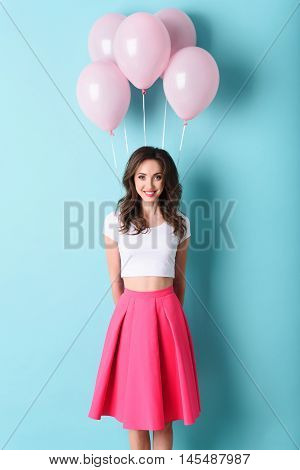 Cheerful girl is hiding pink balloons behind her back. She is looking at camera with happiness and laughing. Isolated on blue background