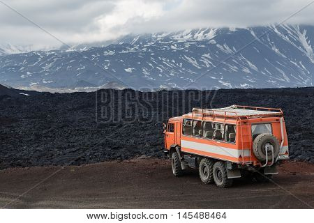 KAMCHATKA PENINSULA RUSSIA - JUNE 24 2016: Russian expedition truck KamAZ (6-wheel drive) on mountain road on background of lava fields and volcanoes. Eurasia Russian Far East Kamchatka Region Klyuchevskaya Group of Volcanoes.