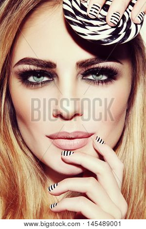 Vintage style close-up portrait of young beautiful sexy girl with smoky eyes, stylish striped manicure and lollipop