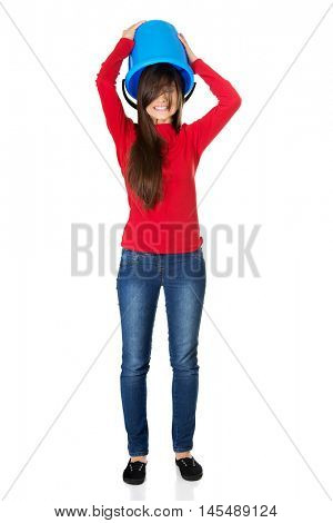 Woman with plastic bucket on head.