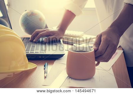 Hands Of Architect Holding Coffee Cup And Working On Laptop
