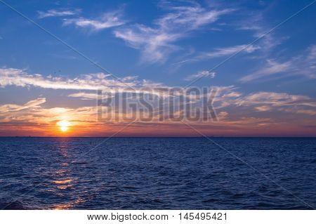 Sunset at Lake Michigan with Chicago Skyline seen on the horizon. Shot at Indiana Dunes National Lakeshore.