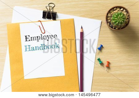 Employee handbook, message on the white paper / business concept / wood desk , copy space / business concept / view from above, top view