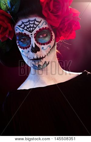 Portrait of scary woman in santa muerte makeup looking at camera.