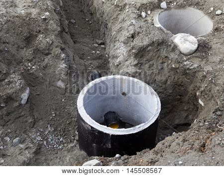 Concrete construction tube pipe in the ground. Building a sewer drain system